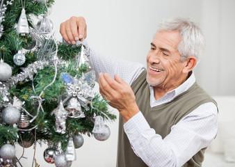 Senior Man Decorating Christmas Tree