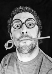 Adult man with glasses with a pen in his mouth