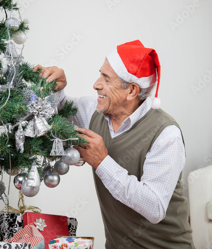 Man Wearing Santa Hat Decorating Christmas Tree