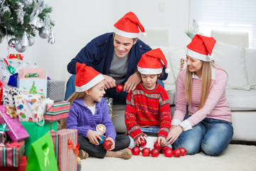 Family With Christmas Decorations And Gifts