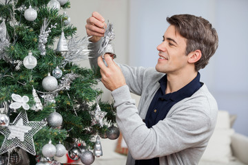 Man Looking At Bell While Decorating Christmas Tree