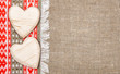 Burlap background bordered by country cloth and wooden hearts