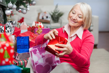 Woman Looking In Bag While Sitting By Christmas Gifts