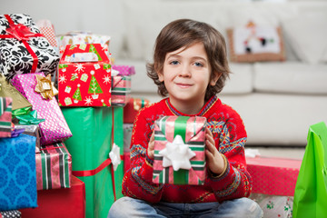 Smiling Boy Holding Christmas Gift At Home