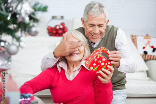 Senior Man Covering Woman's Eyes While Giving Christmas Present