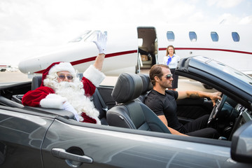 Santa Waving Hand While Driver Driving Convertible Against Priva