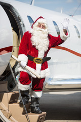 Santa Waving Hand While Standing On Private Jet's Ladder