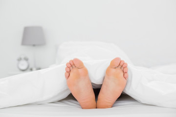 Close-up of bare feet in bed