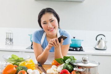 Smiling woman text messaging in front of vegetables in kitchen