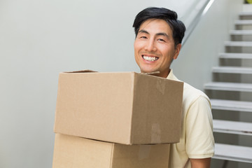 Smiling young man carrying boxes against staircase