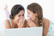 Happy relaxed female friends using laptop in bed