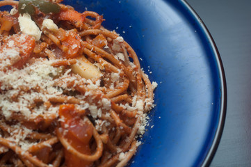 vegetarian wholemeal spaghetti with grated cheese in blue deep d