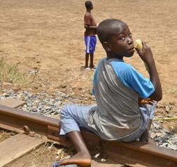 Junge sitzt auf Bahngleis