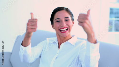 Successful businesswoman sitting on couch and giving thumbs up
