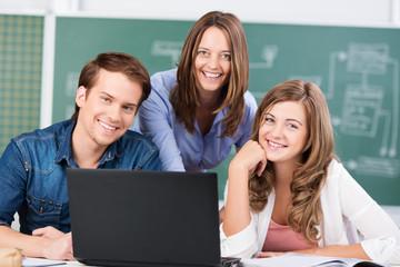 lehrerin mit zwei schülern am laptop