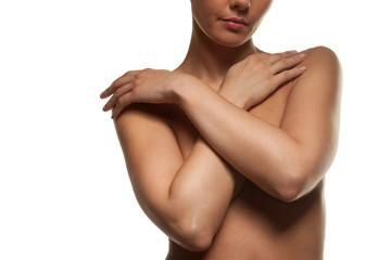 Topless woman with her arms across her breasts