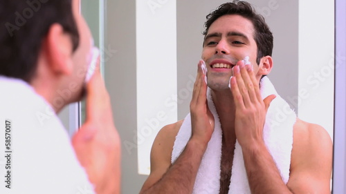 Handsome man applying shaving foam