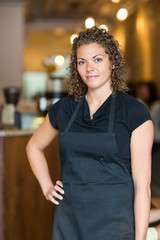 Waitress Standing With Hand On Hip In Cafe