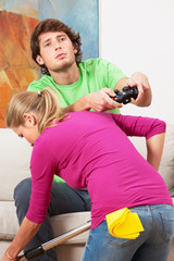 Woman cleaning the house and her husband with console