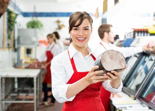 Happy Female Butcher Holding Large Ham - 58570881