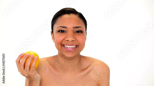 Cute laughing woman holding orange