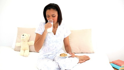 Cute woman sitting on her bed drinking a glass of water