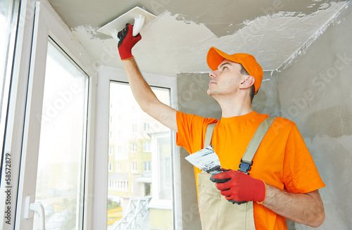 Plasterer at indoor ceiling work