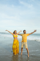 Couple standing on beach with arms outstretched