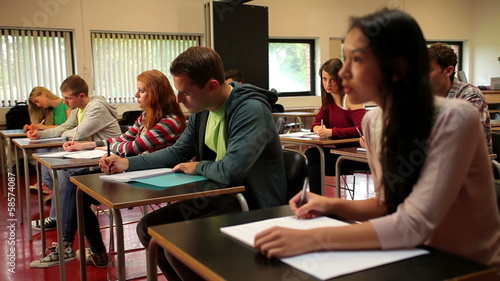 Focused students sitting an exam in a classroom