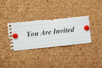 You Are Invited invitation on a cork notice board
