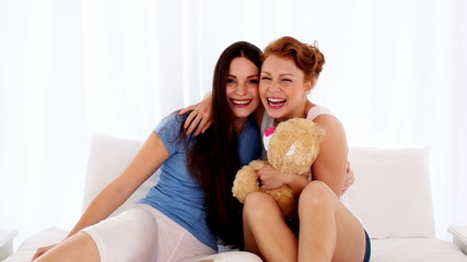 Cute happy woman hugging her friend while holding a teddy bear