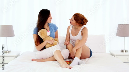 Young beautiful women sitting on bed while chatting