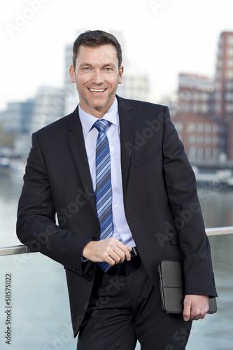 canvas print picture Geschäftsmann lehnt sich an Tablet PC