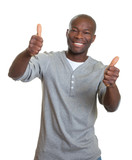 Laughing african man showing both thumbs
