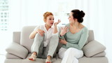 Two attractive women fighting sitting on couch