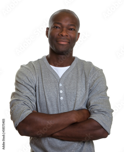 Smiling african man with in a grey shirt with crossed arms