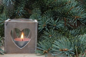 Kerzenschimmer in Holzlaterne mit Tannenzweig