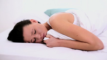 Thoughtful woman lying exhausted in her bed