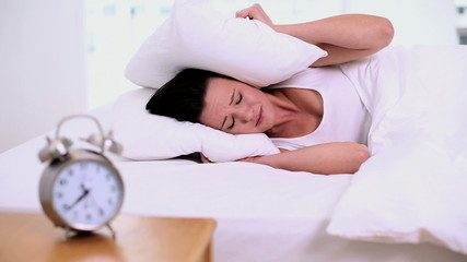 Exhausted woman lying on her bed covering her ears