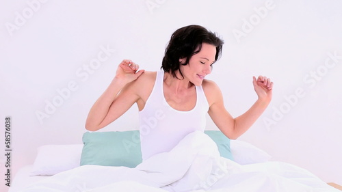 Lovely woman sitting in her bed stretching out