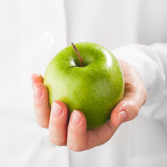 green apple in hand, white background