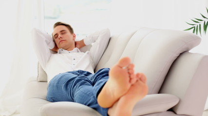 Calm young man sleeping on couch