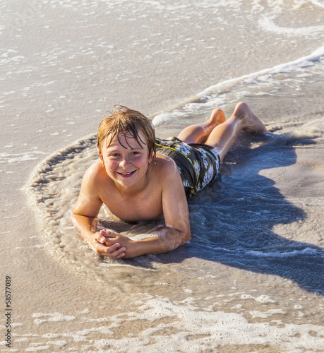 boy lying at the beach and enjoying the sun