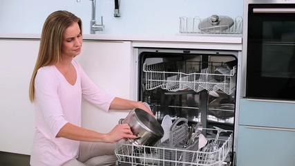 Annoyed woman filling the dish washer