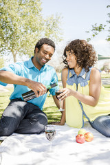 Happy couple enjoying wine during picnic in park