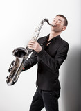 man in black suit playing on saxophone against white background