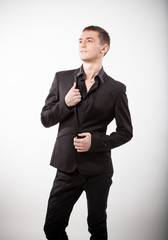 young man in black suit standing against white background