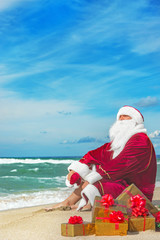 Santa Claus with many golden gifts relaxing at beach  - christma
