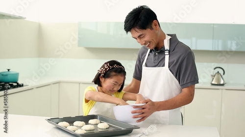 Father and daughter making cookies together