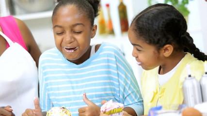 Laughing Ethnic Girls Fun Eating Homemade Cupcakes